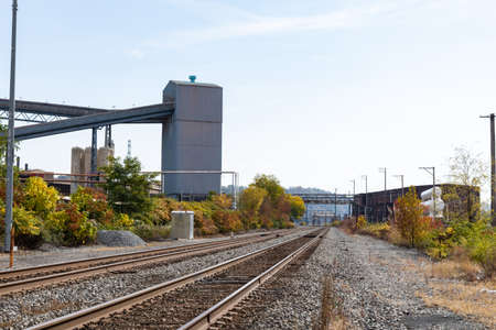 Train tracks running alongside a steel mill industrial complex, fall season with blue and cloudy skies, horizontal aspect
