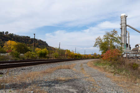 Sweep of train tracks beside an industrial site with white metal gas tanks, fall seasonal colors on a sunny day, horizontal aspect