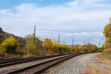 Sweeping view of railroad tracks running into the distance with seasonal fall colors, blue sky and clouds, horizontal aspect