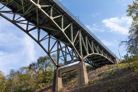 Hillside with concrete supports of an overhead arch bridge, fall season with blue sky, horizontal aspect