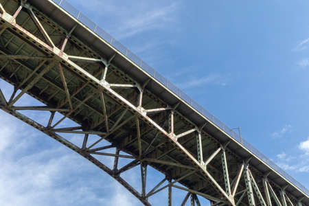 View from underneath an old arch highway bridge silhouetted against a blue sky, creative copy space, horizontal aspect