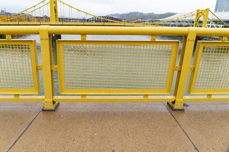Yellow safety railing alongside the sidewalk of a suspension bridge, Pittsburgh Pennsylvania, horizontal aspect