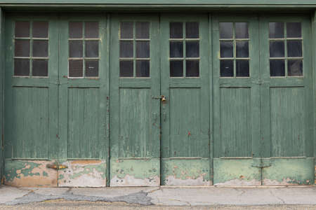 Accordian fold green painted weathered garage doors with windows, creative copy space, horizontal aspect