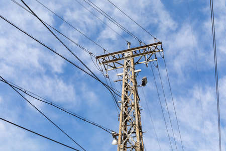 Tall metal electric power tower with lines running in multiple directions against a hopeful blue sky, horizontal aspect