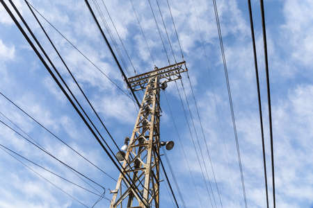 Extreme upward view of an old metal electrical tower with cables attached and alongside against a blue sky with clouds, horizontal aspect 版權商用圖片