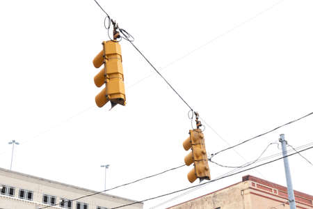 Rear view of traffic signals against an overcast sky, power lines and commercial buildings, horizontal aspect