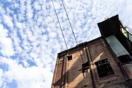Abandoned industrial building, dirty brick exterior, broken out windows, green corrugated against blue sky and clouds copy space, horizontal aspect