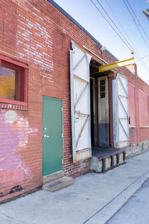 Angled side of a commercial industrial building, red brick and old wood loading dock doors, weathered architectural details, vertical aspect