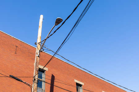 Upward view of a wood power pole and street light set against a red brick industrial building, blue sky copy space, horizontal aspect 版權商用圖片