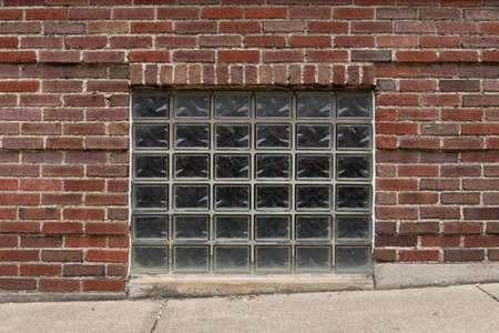 Straight on view of a basement window with glass brick blocks inset, concrete sidewalk on an incline, horizontal aspect