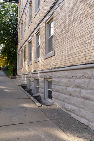 Angled view of inclined sidewalk and building of tan brick and rusticated stone, basement windows, vertical aspect 版權商用圖片