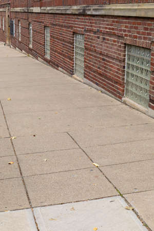 Angled view of a brick building and sidewalk with basement windows filled with glass brick blocks, vertical aspect 版權商用圖片