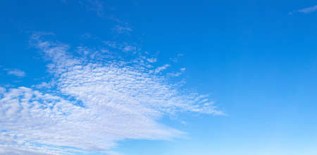 Large panoramic view of bright blue sky with diffuse white clouds, sunny day, creative copy space, horizontal aspect