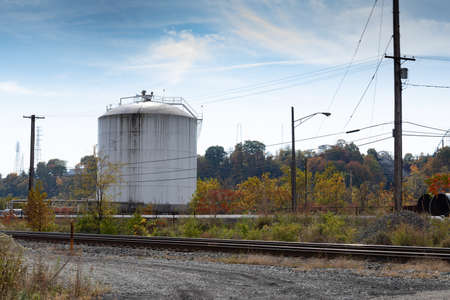 Train tracks alongside gravel access road and industrial tank, power lines, fall season, horizontal aspect
