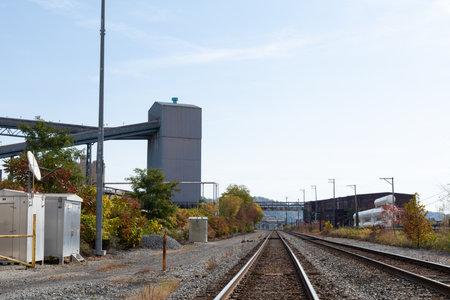 View straight down the center of train tracks running alongside industrial areas, fall season, horizontal aspect