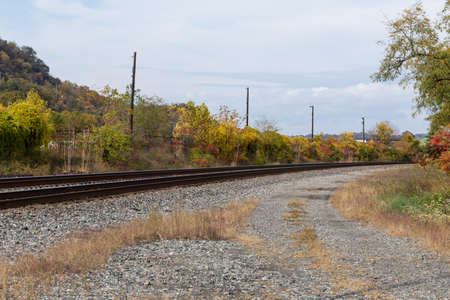 Curved train tracks running through a rural area, fall landscape with autumn leaves, horizontal aspect 版權商用圖片