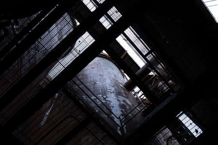 Light streaming down into a dark industrial structure through grates, creative copy space, horizontal aspect