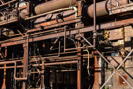 Abandoned manufacturing facility structure, rusted pipes and tubes, horizontal aspect 版權商用圖片