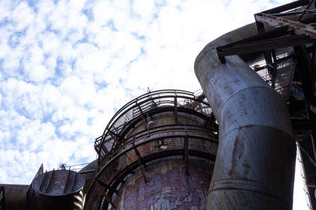 Tubes and blast furnace structure with circular grate catwalks, blue sky with clouds copy space, horizontal aspect 版權商用圖片