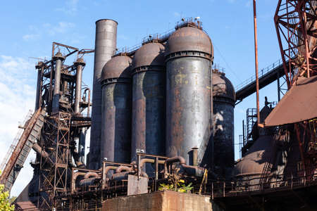 Abandoned steel mill industrial structures, rusting blast furnaces against blue skies, horizontal aspect