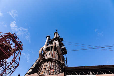 Old steel manufacturing facility structures seen from below, vivid blue sky with clouds, horizontal aspect 版權商用圖片