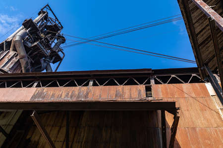 View looking up at derelict industrial structures, blue sky copy space, horizontal aspect 版權商用圖片