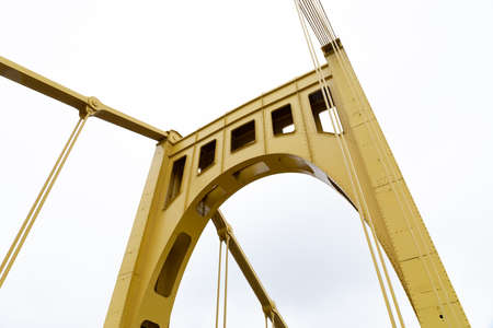 Yellow upright of a self anchored suspension bridge seen from below, white sky, horizontal aspect