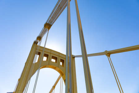 Sun behind the upright support of a self anchored suspension bridge, blue sky, horizontal aspect