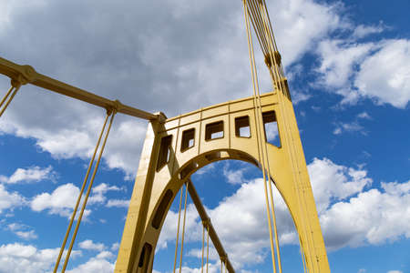 Riveted metal self anchored suspension bridge painted yellow against a bright blue sky with white puffy clouds, horizontal aspect