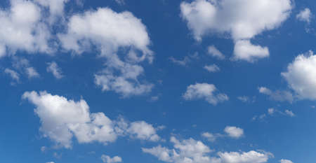 Bright blue sky with puffy white clouds panoramic view, horizontal aspect 版權商用圖片