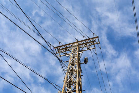 View looking up at a tall metal power tower and cables, deep blue sky with light clouds, horizontal aspect