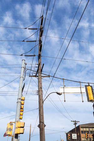 Composition of very tall power pole, traffic signals, and power lines before blue sky with light clouds, vertical aspect