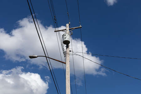 Light wood power pole with transformer and street light before a deep blue sky with white puffy clouds, horizontal aspect