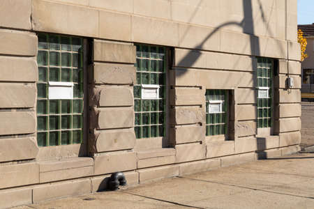 Commercial or municipal building with basement windows replaced with glass brick blocks for security, crumbling dressed limestone exterior and concrete sidewalk, horizontal aspect