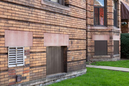 Old brick apartment building with basement windows filled with mixed bricks, vents, and wood boards, horizontal aspect 新聞圖片
