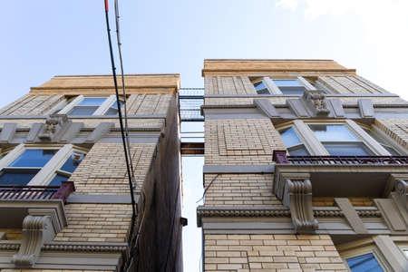 Upward view of space between two apartment buildings revealing metal catwalks between the buildings, horizontal aspect