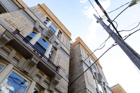 Extreme upward view of old light brick apartment buildings with power pole and lines, horizontal aspect Foto de archivo