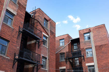 Urban landscape rear view of old brick apartment buildings with black metal fire escapes against a bright blue sky, horizontal aspect