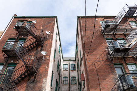 Centered view of a light well between apartment building wings, metal fire escapes, urban housing composition, horizontal aspect
