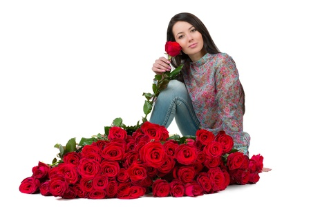 flowergirl: Cute brunette sitting beside a large bouquet of red roses Stock Photo