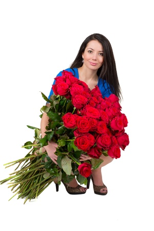 Brunette woman with a big bouquet of red roses photo