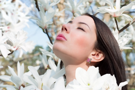 Young woman surrounded by flowers of Magnolia photo
