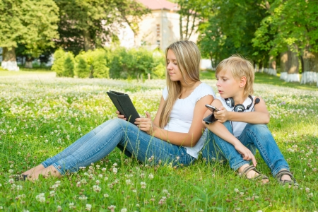 Boy and girl sitting in the park and enjoy the tablet