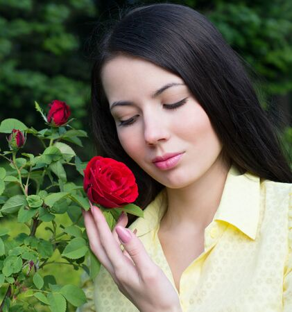 Portrait of a Woman with a red rose in the garden photo