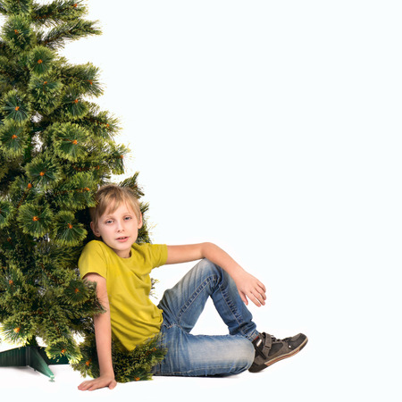 Boy sitting under the Christmas tree photo