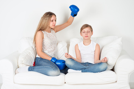 Boy meditating, girl in boxing gloves wants to hit him photo