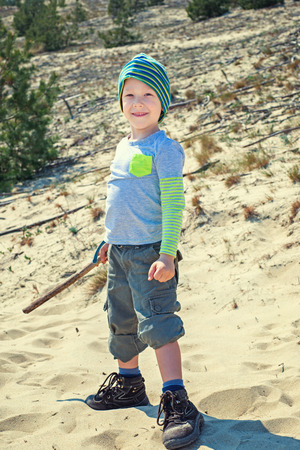 baby 4 5 years: Boy with a stick walks on nature Stock Photo