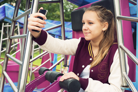 13 14 years: Teen Girl Makes Selfie on the Carousel Stock Photo