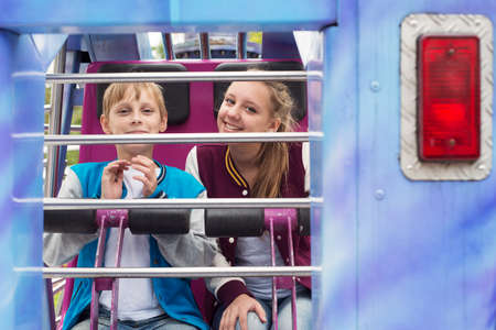 12 13: Teenagers sitting on the extreme carousel