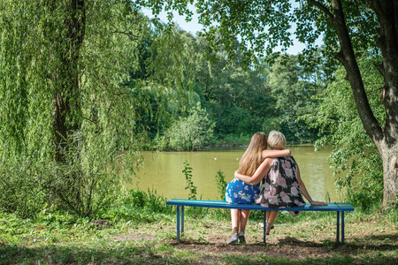 two generations: Two women of different generations sitting on a bench near a pond in the summer. Mother and daughter hugging. Grandmother and granddaughter.
